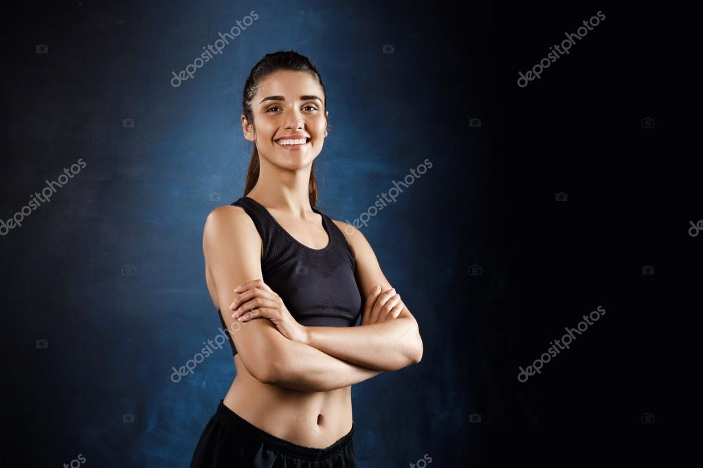 b564880032e Όμορφη sportive κοπέλα ποζάρει με σταύρωσε τα χέρια πάνω από το σκούρο  φόντο — Φωτογραφία Αρχείου