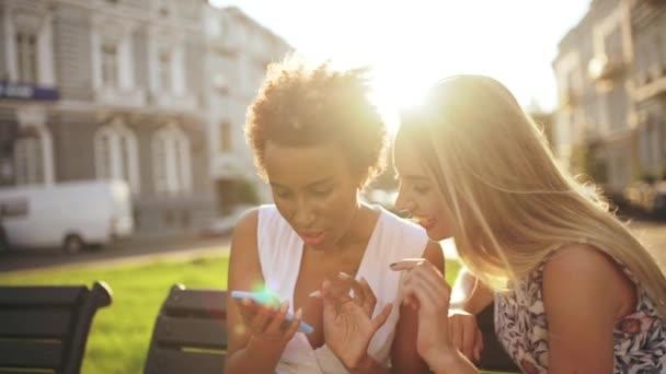 Krásné dívky mluví, usměvavý, při pohledu na telefon, sedí v městském parku. Zpomalený pohyb