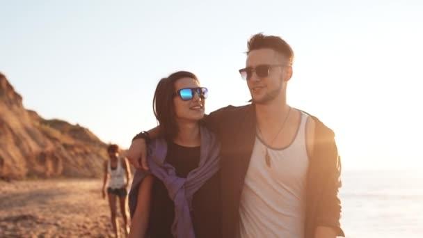 Friends smiling, laughing, speaking, walking at seaside at sunrise. Slow motion.