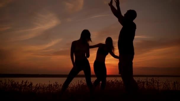 friends dancing, rejoicing in field at sunrise