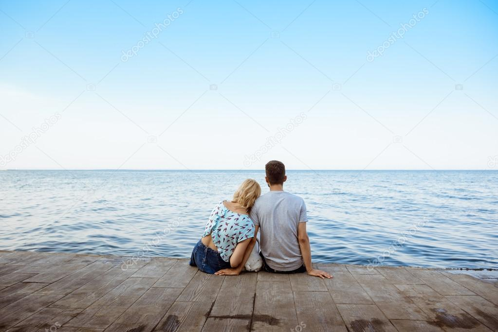 Couple De Dos couple sitting back to camera with french bulldog near sea. — stock