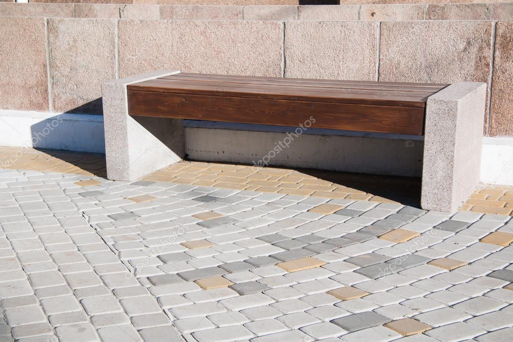 Wooden bench with stone foundation in middle of paving slabs.