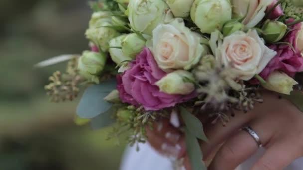 Nevěsta drží svatební kytice z růží, ostružiny a zeleň