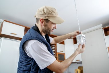 A male electrician fixing light on the ceiling.