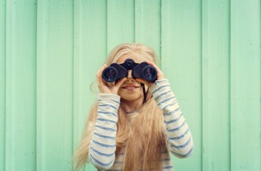Cute little girl stands near a turquoise wall and looks binoculars. Space for text