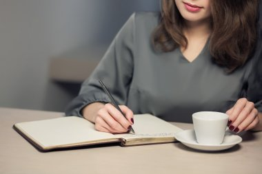 young adult female has coffee break in cafe and writing notes in diary or notepad