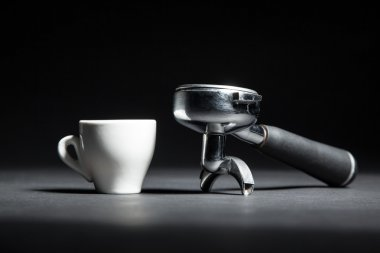 artistic studio shot of holder for coffee machine and white cup;