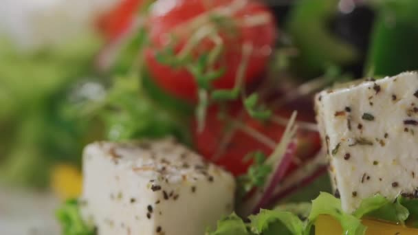 closeup of fresh greek salad with herbs and spice on square white plate