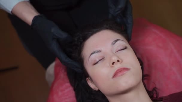 pretty female at cosmetician on rejuvenating head or facial massage procedure