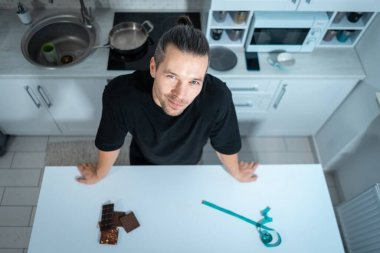 sportive man on diet with chocolate bar and measuring tape at modern kitchen
