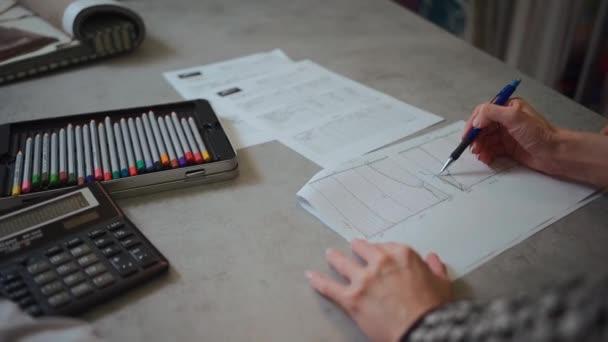 návrhář interiérů ruce kreslení náčrt nebo výběr opony s klientem ve studiu