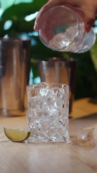 Video von der Hand, die Eiswürfel ins Glas gibt oder einen kalten Cocktail zubereitet