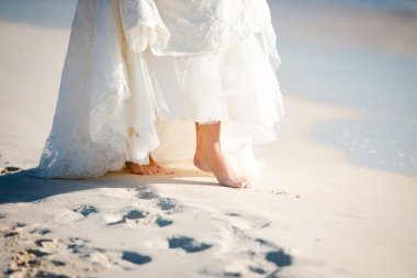 Closeup of bare feet of a bride on the beach in Mexico, Riviera Maya. Destination wedding.