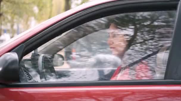 Das schöne Mädchen in einem roten Kleid in einem roten Auto rollt das Fenster herunter und lächelt. Autofahrerin unterwegs
