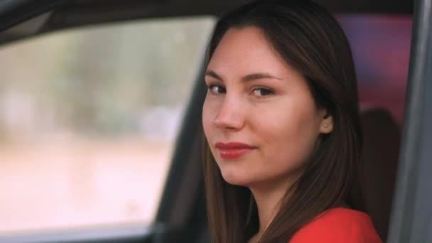 Eine schöne junge Fahrerin mit rotem Lippenstift im roten Kleid dreht sich um und blickt direkt in die Kamera. Die Frau lächelt. Rotes Auto