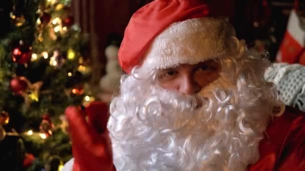 Az idősebb Télapó, buja fehér szakállal, egy ujját tépi a csintalan gyerekeknek. Karácsony és újév. Ünnep és ünneplés. Közelről. Posztrait. 4K