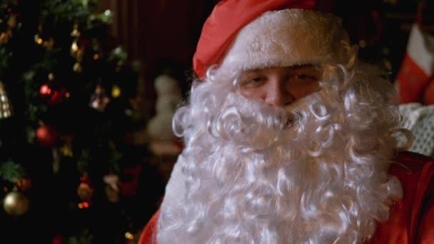 Az idősebb Télapó, buja fehér szakállal simogatja a szakállát. Karácsony és újév. Közelebb, portré. Nyaralás és nyaralás. 4K. Lassú mozgás.