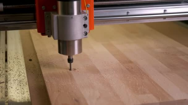 CNC machine cuts a cutting Board out of wood along an automated route. Carving.