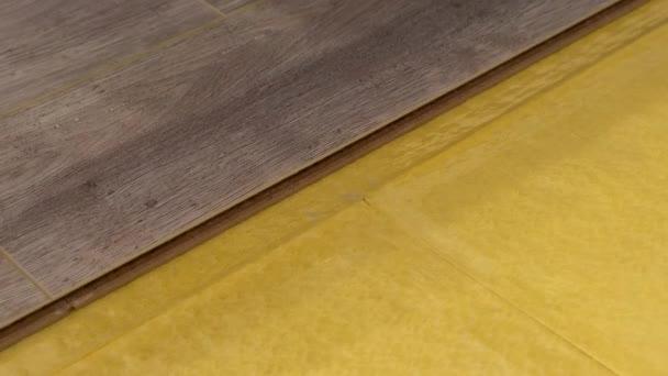 Položení laminátové podlahy v detailu. Technologie a proces. Ruce stavitele zblízka. Oprava podlahy