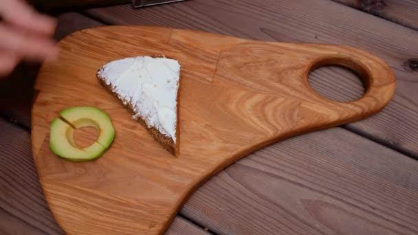 Egy nő keze kettévág egy szelet avokádót egy acél késsel, és egy vajas szendvicsre teszi. Aztán kaprot rak a tetejére. Reggeli készítése
