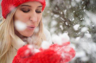 Winter time walking on street. Enjoying snowfall, expressing positivity, smiling to camera, joyful cheerful, new year mood.