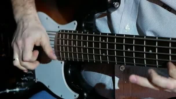 Zenész basszusgitározik, közelről.