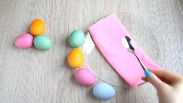 Ruka klade lžičkou vedle obarvená vejce na sváteční velikonoční stůl