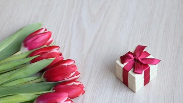 Fehér asztal található tulipán piros-fehér és piros Ajándékdoboz.