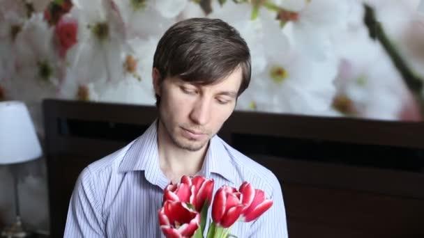 Pohledný muž, dívat se na květiny - tulipány a prezentuje je v kameře