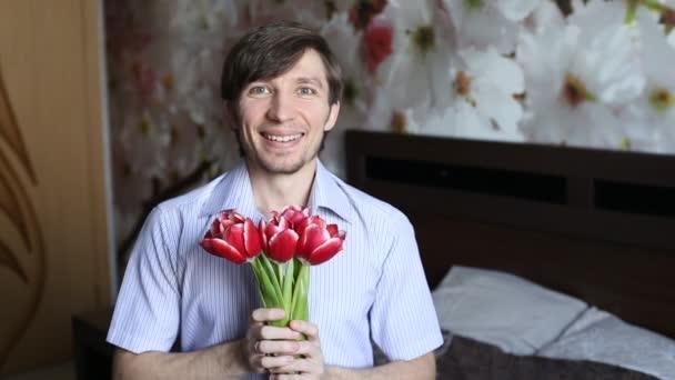 Krásný člověk s láskou představuje květiny s kamerou - tulipány
