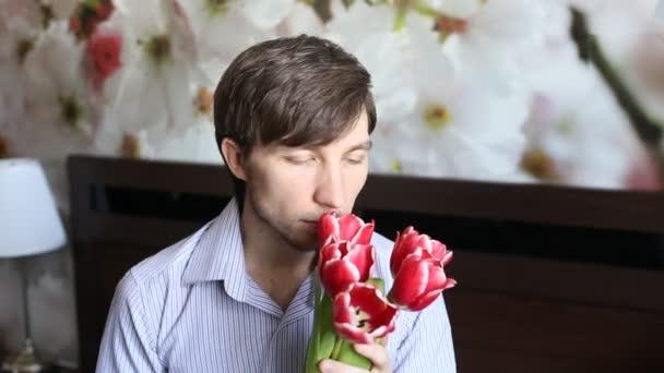 Atraktivní muž je vonící květy a zůstat v blažený úsměv