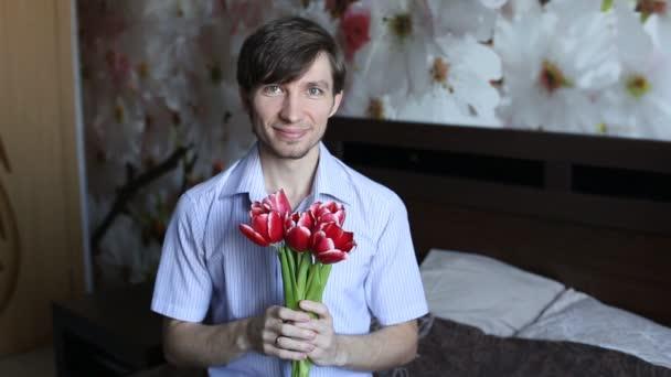 Muž ukazuje, že chce dát květiny od srdce