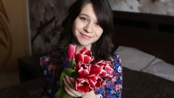 krásná dívka čichat květiny, při pohledu na fotoaparát, s úsměvem, flirtování