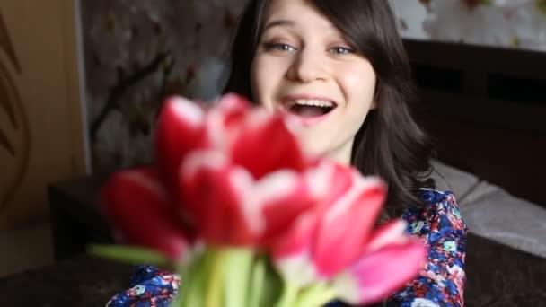 Dávají květiny k ženě, ona se usmívá, zvedne květiny a zkoumá jejich