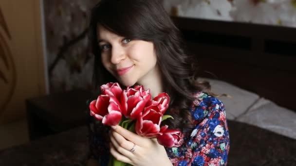 Krásná dívka drží květiny, při pohledu na fotoaparát, s úsměvem, flirtování