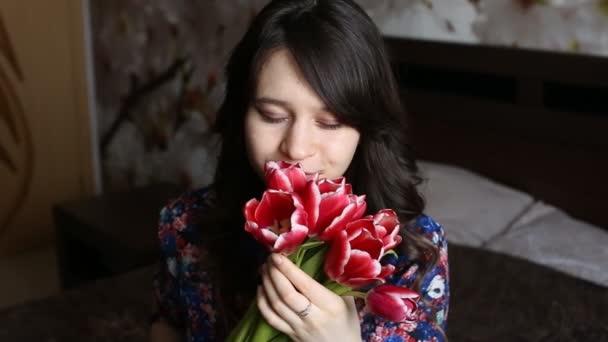 Hezká holka čichání květina, hravě se dívá na kameru a usmívá se