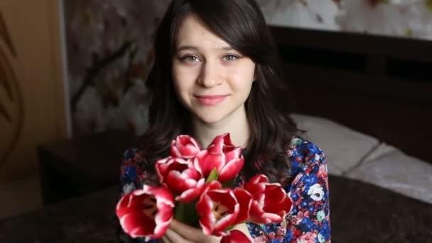 Krásná žena, usmívá se prodlouží květiny - tulipány s kamerou