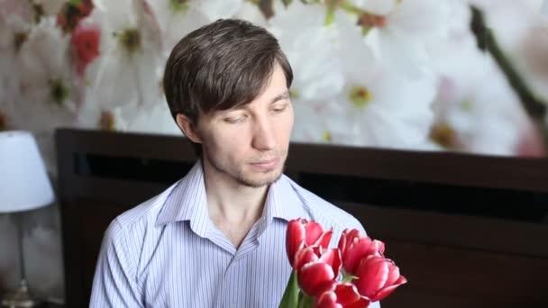 Atraktivní muž při pohledu na květiny a květy dává k fotoaparátu