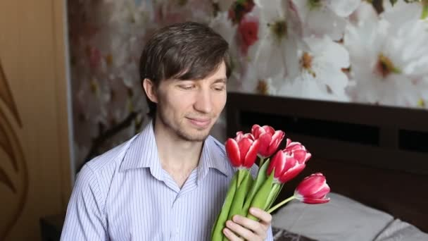 Attractive man sends a kiss and gives flowers.