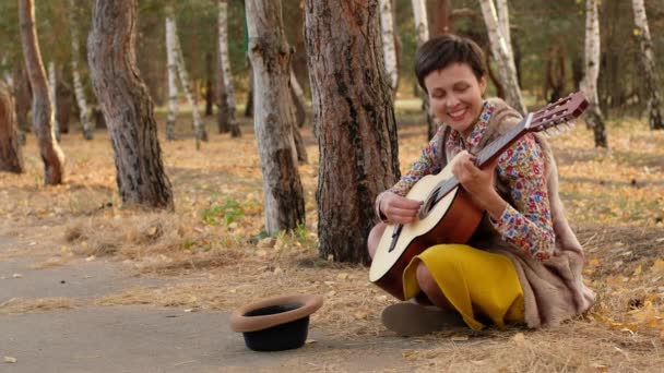 Beautiful woman in a hat playing acoustic guitar in park. Street musician performer sitting on ground performs a song asking for money.