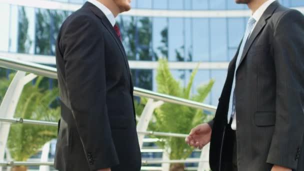 Businessmen talking near the office building