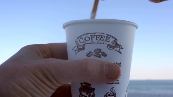 Ruka muže míchání hrnek na kávu