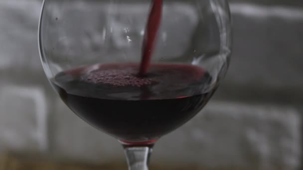 Red wine in a glass close-up on a white brick wall background.