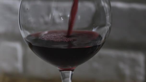 Červené víno ve sklenici close-up na bílém cihlové zdi pozadí.