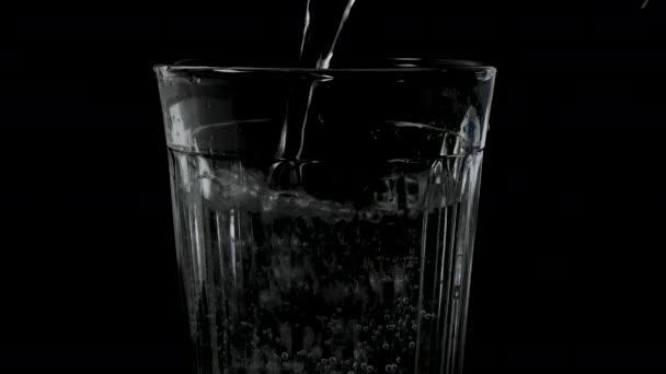 Minerální voda ve sklenici na černém pozadí makro fotografie, nalévání vody do sklenice, pitná voda zblízka