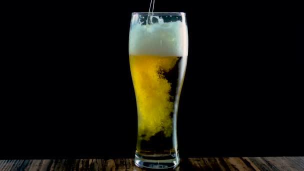 A világos sört egy fekete hátterű söröspohárba öntik, közelről pedig egy pohárba.