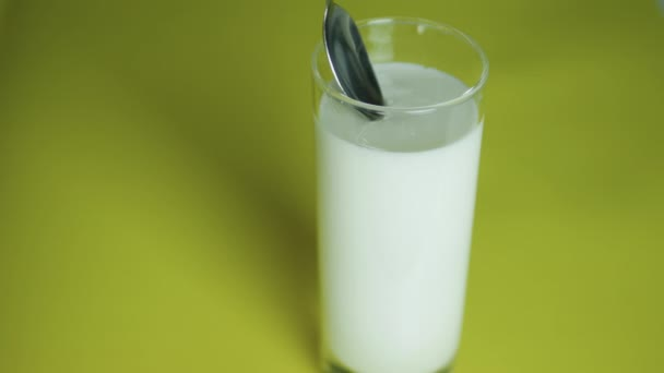 Odborník udělá vzorek mléčných výrobků, vyšetří mléko k vyšetření, sklenici kefíru na žlutém pozadí. Sbírejte lžící kefíru