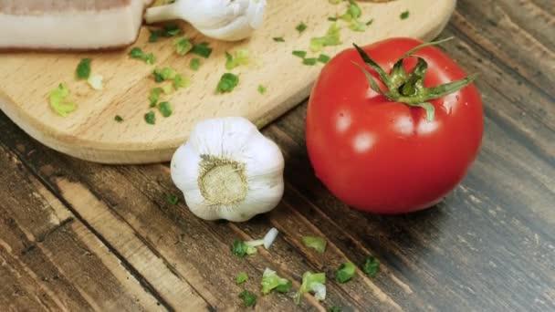 Frisches Naturgemüse auf dem Küchentisch, Tomaten mit Knoblauch und Brot, Speck auf einem Torfblech. Zum Kochen