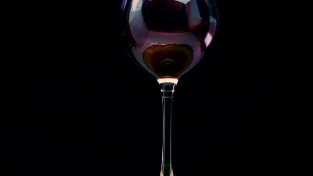 Pour red wine into a wine glass on a black background. Wine on wood
