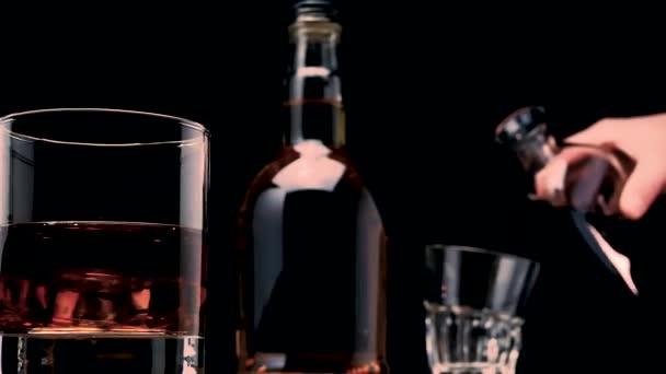 Detailní záběr whisky s ledem ve sklenici. Nalít whisky do sklenice na rozmazaném pozadí. Alkoholický nápoj na černém pozadí.